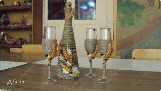 Бутылка обмотана иловыми ветками, поверх льняная нить и нитка флористическая( вроде бы так называется. украсила колосками(покрасила балончиком), ромашки слепила из пластики, бусинки, листики. фото 1