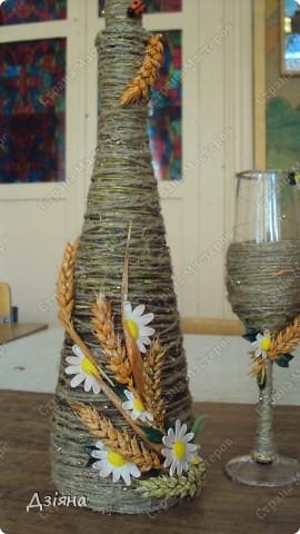 Бутылка обмотана иловыми ветками, поверх льняная нить и нитка флористическая( вроде бы так называется. украсила колосками(покрасила балончиком), ромашки слепила из пластики, бусинки, листики. фото 2