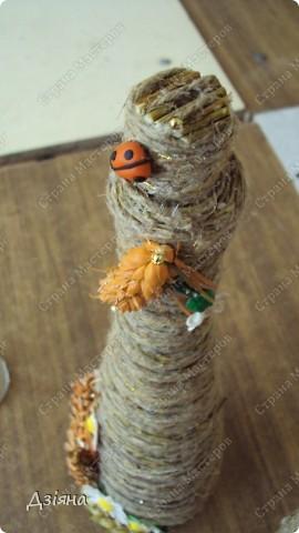 Бутылка обмотана иловыми ветками, поверх льняная нить и нитка флористическая( вроде бы так называется. украсила колосками(покрасила балончиком), ромашки слепила из пластики, бусинки, листики. фото 4
