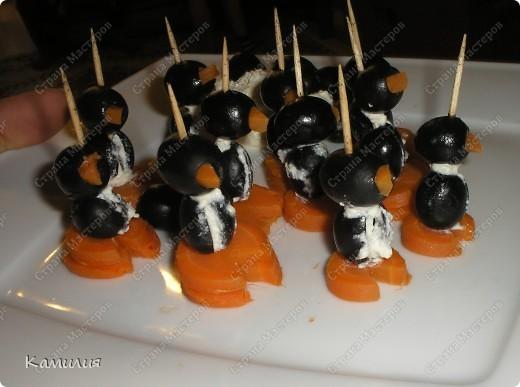 Пингвины  Морковь, маслины, сыр (брынза или фета), шпажки или зубочистки.  Морковь отварить, нарезать кольцами, вырезать из каждого колечка треугольничек, который и послужит клювом для пингвина, другая часть послужит нижней частью (лапками). Маслину-тулуп разрезаем и ложим внутрь кусочек сыра. В маслину-голову вставляем клювик-морковь. Собираем пингвина на шпажку.  Приятного аппетита.  У меня использован домашний творог, потому и мои пингвинчики получились как будто с шарфиками. фото 1