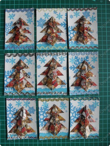 Нравятся мне такие ёлочки-оригами из новогодней упаковочной бумаги. Я в прошлом году такие открытки делала. Решила теперь приспособить их для АТС. Фон - салфетка со снежинками. Мама принесла новую блестящую тесьму, я её сразу приспособила. Снежинки дырокольные.  фото 1