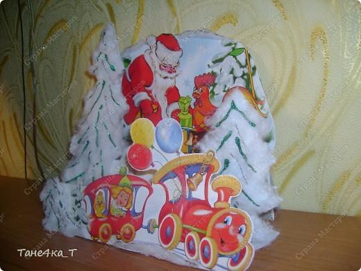 Здесь всё очень просто. Сложила картон гармошкой в три ряда. На первый приклеила Деда Мороза */вырезала с коробки конфет/*, на второй ёлочки из картона, обклеила ватой и нанесла зеленый гель с блестками, и на первый ряд паровозик. Получилась вот такая объемная открыточка.