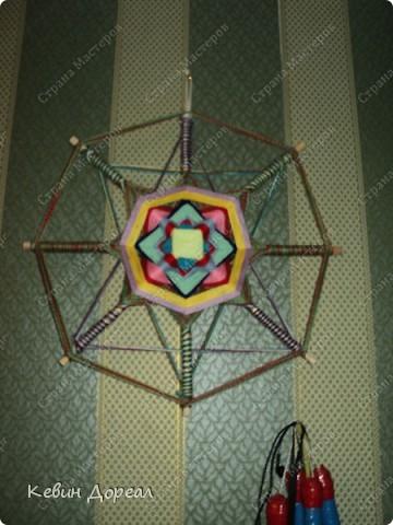 На заднем плане в Мандалу вплетена звезда Давида или же символы мужского и женского начала.