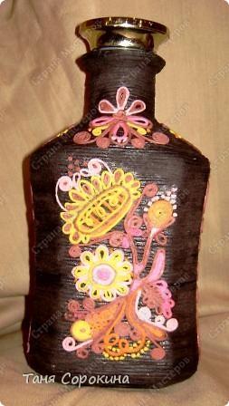"""И снова я к вам с разновидностями пейп-арта. Эта бутылочка сделана """"под вышивку"""", вся её поверхность обвёрнута нитями из салфетки тёмно-коричневого цвета, а сверху узоры сделаны цветными салфеточными нитями. Мой МК по изготовлению картин или поделок из цветных нитей здесь http://stranamasterov.ru/node/315194. Эти бутылочки делали мать и дочь - Ира и Даша, которые  у меня занимаются в студии. Эту сделала мама Ира. К сожалению, фото не передаёт правильно цвета, снимали в студии при электрическом освещении... фото 2"""