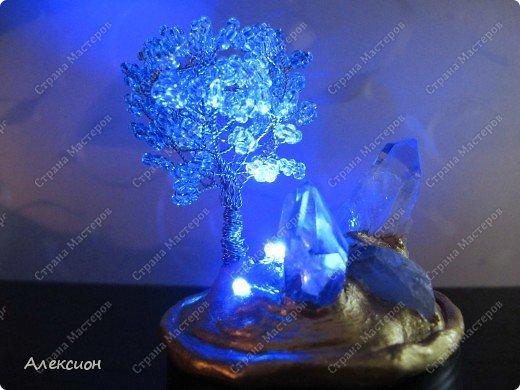 """Обычное бисерное дерево с подсветкой от четырёх синих свето-диодов по 3 В каждый, вклеянных в основу. Окружают дерево настоящие кристаллы горного хрусталя. Композиция смонтирована на баночке из под сметаны, запитана от батарейки 12 В и окрашена акриловой краской """"Геральдическое золото"""" фото 1"""