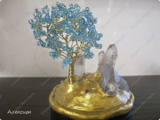 """Обычное бисерное дерево с подсветкой от четырёх синих свето-диодов по 3 В каждый, вклеянных в основу. Окружают дерево настоящие кристаллы горного хрусталя. Композиция смонтирована на баночке из под сметаны, запитана от батарейки 12 В и окрашена акриловой краской """"Геральдическое золото"""" фото 2"""