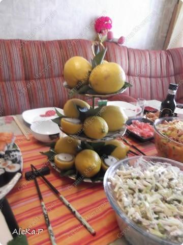 Ни так давно у мужа был день рождения, муж праздновать совсем не хотел, но в тайне от него я устроила ему сюрприз, он любит японскую кухню, вот я и приготовила вечеринку в японском стиле. Муж был приятно удивлен и попросту обалдел:)))))) Стены украшали веера, бумажный фонарик, на столе тоже очень много подходящих атрибутов. Я выглядела в виде гейши, правда беременной гейши:)))))))))))), в кимоно смотрелась смешно, фотографию выставлять не буду. Музыкальный фон тоже был из национальных мелодий.   На этой фотографии изображена композиция из лимонов, вишневых листочков и свечей, это был своеобразный подсвечник. фото 1