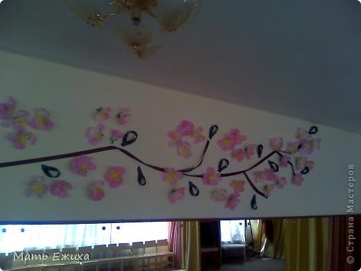 Была цель - с минимальными затратами и повреждением новых обоев украсить стену к празднику. Мы прикрепили из коричневой ленты огромную ветку, добавили петельки из зеленой ленты - листики... фото 3