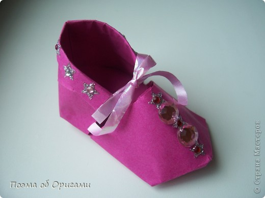 В некоторых странах есть традиция дарить пинетки новорожденным. Даже если в семье за последнее время не происходило пополнения, вот такой оригами-башмачок с оригами-цветами станет красивым украшением для интерьера.  фото 1