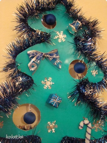 Такую елочку я делала в прошлом году в детский садик. Идею нашла в одном журнале (саму форму и дырочки для игрушек), а я прицепила ище гирлянду и оформила по своему вкусу.  фото 2