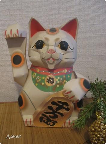 """Манеки Неко (Maneki Neco)- японский кот, призывающий удачу.  Про этого кота сущестует множество легенд. Одна из них гласит:  """"Был в старом Эдо (Токио) бедный храм Котоку, священник которого держал кота по имени Тама и все жаловался коту на трудную жизнь. И в шутку попрекал Таме, что он не приносит он дары в храм. Но однажды важный господин Наотака Ли попал в сильную грозу около храма и спрятался от дождя под деревом. Вдруг он увидел как из-за дверей храма кот машет ему лапкой. Господин Наотаку поспешил к храму и в ту же минуту молния спалила дерево, под которым он прятался, до тла. В благодарность за спасение Наотака сделал храм родовым храмом Ли, построил новое большое здание и дал ему новое название – Гоутокаджи (Gotoku-ji). После смерти Тама, кот был похоронен в храме со всем почетом, а в память о его поступке изготовили глиняного котика Манеки Неко. Его изображения красуются в Зале Божества Милосердия. У ворот Гоутокаджи всегда продается много глиняных Манеки Неко и каждый может обзавестись котом на счастье"""". Вот и мы сделали кота на счастье... фото 1"""