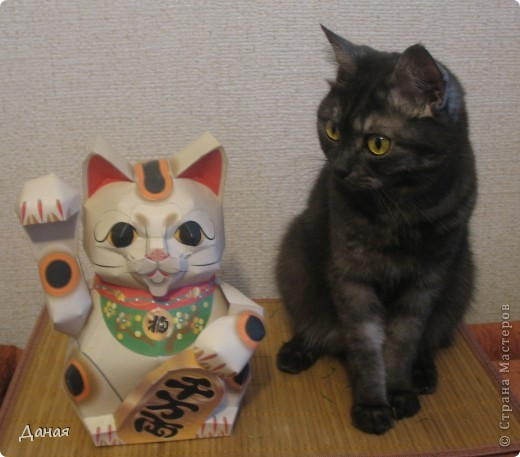 """Манеки Неко (Maneki Neco)- японский кот, призывающий удачу.  Про этого кота сущестует множество легенд. Одна из них гласит:  """"Был в старом Эдо (Токио) бедный храм Котоку, священник которого держал кота по имени Тама и все жаловался коту на трудную жизнь. И в шутку попрекал Таме, что он не приносит он дары в храм. Но однажды важный господин Наотака Ли попал в сильную грозу около храма и спрятался от дождя под деревом. Вдруг он увидел как из-за дверей храма кот машет ему лапкой. Господин Наотаку поспешил к храму и в ту же минуту молния спалила дерево, под которым он прятался, до тла. В благодарность за спасение Наотака сделал храм родовым храмом Ли, построил новое большое здание и дал ему новое название – Гоутокаджи (Gotoku-ji). После смерти Тама, кот был похоронен в храме со всем почетом, а в память о его поступке изготовили глиняного котика Манеки Неко. Его изображения красуются в Зале Божества Милосердия. У ворот Гоутокаджи всегда продается много глиняных Манеки Неко и каждый может обзавестись котом на счастье"""". Вот и мы сделали кота на счастье... фото 2"""
