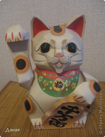 """Манеки Неко (Maneki Neco)- японский кот, призывающий удачу.  Про этого кота сущестует множество легенд. Одна из них гласит:  """"Был в старом Эдо (Токио) бедный храм Котоку, священник которого держал кота по имени Тама и все жаловался коту на трудную жизнь. И в шутку попрекал Таме, что он не приносит он дары в храм. Но однажды важный господин Наотака Ли попал в сильную грозу около храма и спрятался от дождя под деревом. Вдруг он увидел как из-за дверей храма кот машет ему лапкой. Господин Наотаку поспешил к храму и в ту же минуту молния спалила дерево, под которым он прятался, до тла. В благодарность за спасение Наотака сделал храм родовым храмом Ли, построил новое большое здание и дал ему новое название – Гоутокаджи (Gotoku-ji). После смерти Тама, кот был похоронен в храме со всем почетом, а в память о его поступке изготовили глиняного котика Манеки Неко. Его изображения красуются в Зале Божества Милосердия. У ворот Гоутокаджи всегда продается много глиняных Манеки Неко и каждый может обзавестись котом на счастье"""". Вот и мы сделали кота на счастье... фото 3"""