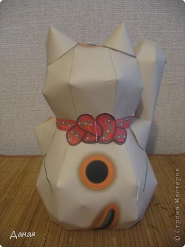 """Манеки Неко (Maneki Neco)- японский кот, призывающий удачу.  Про этого кота сущестует множество легенд. Одна из них гласит:  """"Был в старом Эдо (Токио) бедный храм Котоку, священник которого держал кота по имени Тама и все жаловался коту на трудную жизнь. И в шутку попрекал Таме, что он не приносит он дары в храм. Но однажды важный господин Наотака Ли попал в сильную грозу около храма и спрятался от дождя под деревом. Вдруг он увидел как из-за дверей храма кот машет ему лапкой. Господин Наотаку поспешил к храму и в ту же минуту молния спалила дерево, под которым он прятался, до тла. В благодарность за спасение Наотака сделал храм родовым храмом Ли, построил новое большое здание и дал ему новое название – Гоутокаджи (Gotoku-ji). После смерти Тама, кот был похоронен в храме со всем почетом, а в память о его поступке изготовили глиняного котика Манеки Неко. Его изображения красуются в Зале Божества Милосердия. У ворот Гоутокаджи всегда продается много глиняных Манеки Неко и каждый может обзавестись котом на счастье"""". Вот и мы сделали кота на счастье... фото 5"""