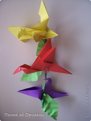 Двигающиеся модели неспроста пользуются большим успехом. Обычный сложенный квадрат способен буквально ожить в руках мастера. Каждая из этих трех птичек умеет делать что-то свое.  Желтый птенец, как и подобает птичьим малышам - постоянно голоден, а потому, характерно для этого, то открывает широко клюв, то лишь ненадолго его прикрывает. Его придумал Хуан Гимено из Испании. Красная птица умеет махать крыльями. В своем мастерстве она по праву считается одной из лучших в мире, так как ее крылья во время полета совершают широкие взмахи, почти сходясь сверху и снизу тела. Ее придумал Самуэль Рандлетт из США. Синяя птица умеет ловко клевать зернышки из кормушки. Эта модель, в отличии от предыдущих, известна очень давно и легко складывается с небольшой вариацией из классической модели журавлика. Вся конструкция крепится к ленте с помощью не больших канцелярских прищепочек.  В любой момент каждая из них готова от нее оторваться, что бы с радостью заняться своим излюблиным занятием в Ваших руках. фото 1