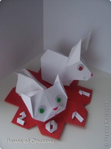 В качестве символа 2011 год делят между собой два животного китайского календаря. Видимо, это не простое совпадение, ведь у них и правда много общего. Оба с кротким нравом и пушистой шубкой.  Этого кролика придумал Стефан О`Хонор, а котика – Джо Накашима.  Подставка в форме четырех сердец – модель Френсиса Оу. Вся композиция сложена из квадратов одинакового размера(2 красных и 2 белых), в данном случае 20х20см. Как сложить из полос бумаги цифры – можете вспомнить в этом МК: https://stranamasterov.ru/node/127038 фото 77