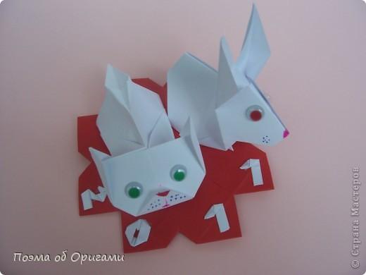 В качестве символа 2011 год делят между собой два животного китайского календаря. Видимо, это не простое совпадение, ведь у них и правда много общего. Оба с кротким нравом и пушистой шубкой.  Этого кролика придумал Стефан О`Хонор, а котика – Джо Накашима.  Подставка в форме четырех сердец – модель Френсиса Оу. Вся композиция сложена из квадратов одинакового размера(2 красных и 2 белых), в данном случае 20х20см. Как сложить из полос бумаги цифры – можете вспомнить в этом МК: https://stranamasterov.ru/node/127038 фото 1