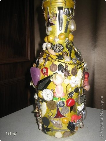 """Ваза """"Магнит времени"""" сделана из винной бутылки с широким горлышком. Предварительно бутылка загрунтована. Затем дважды покрашена желтой акриловой краской, вначале обычной, а потом с металлическим золотым блеском. На вазу наклеены клеем """"Момент"""" все, что оказалось лишним и вышедшим из моды в шкатулках у меня и дочери - старая бижутерия, оставшиеся по одной сережки, мелкие детальки, часы дедушки, бабушки и мои, цепочки, бусины, значки, монетки разные, ключики, застежки, всякие металлические блестяшки, пайетки.... Затем все это планировалось вскрыть золотой краской из аэрозольного баллончика... Но тут восстали дети и муж, и не разрешили это делать, мотивируя тем, что не будет видно предметов. Так я и оставила.... фото 1"""