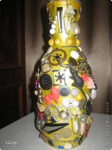 """Ваза """"Магнит времени"""" сделана из винной бутылки с широким горлышком. Предварительно бутылка загрунтована. Затем дважды покрашена желтой акриловой краской, вначале обычной, а потом с металлическим золотым блеском. На вазу наклеены клеем """"Момент"""" все, что оказалось лишним и вышедшим из моды в шкатулках у меня и дочери - старая бижутерия, оставшиеся по одной сережки, мелкие детальки, часы дедушки, бабушки и мои, цепочки, бусины, значки, монетки разные, ключики, застежки, всякие металлические блестяшки, пайетки.... Затем все это планировалось вскрыть золотой краской из аэрозольного баллончика... Но тут восстали дети и муж, и не разрешили это делать, мотивируя тем, что не будет видно предметов. Так я и оставила.... фото 2"""