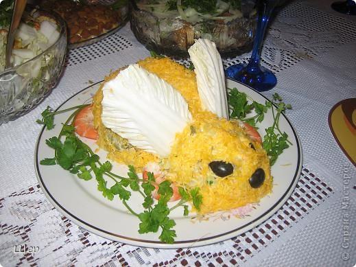 """Новогодний салат """"Кролик"""" Вам понадобится:  300 г куриного филе 200 г майонеза 150 г чернослива 100 г грецких орехов 100 г твердого сыра 100 г сливочного плавленого сыра 4 яйца 2 моркови 1 пекинская капуста зелень (базилик, петрушка и укроп) Способ приготовления: Отварное куриное филе разобрать на волокна и порезать, морковь, яйца сварить, потереть на терке по отдельности. Нарезать тонкой соломкой чернослив, натереть на терке по отдельности сыры, измельчить грецкие орешки. Соединить морковь, яйца, курицу, чернослив, орехи и сыр, перемешать, добавив майонез, разделить на 2 части – поменьше и побольше. Выложить большую часть салата в виде туловища, меньшую – в виде головы кролика. Сделать ушки из пекинской капусты, посыпать кролика тертым сыром, глаза сделать из половинки маслинки, носик тоже."""