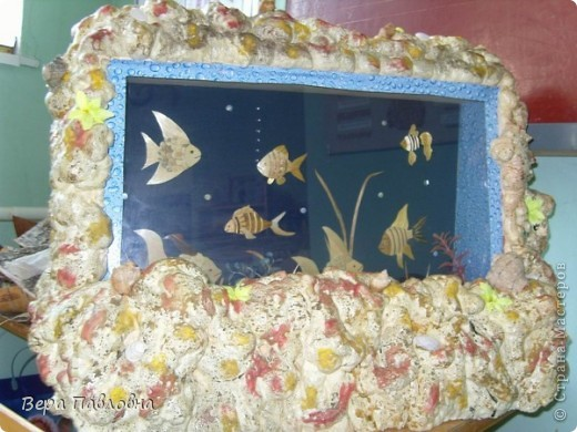 Для работы был сделан каркас из дерева со стеклянной витриной. На задней стенке имитация воды, где плавают рыбки, выполненные из соломки. Каркас отделан монтажной пеной и раскрашен под цвет камней. Внутри имеется подсветка фото 2