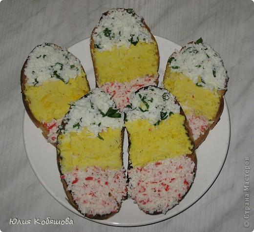 У вареных яиц отделить белки от желтков.  Сыр и белки натереть на средней терке, смешать со сметаной или майонезом   (при желании в массу можно добавить продавленный через пресс зубчик чеснока)   и разделить на 3 части.  В первую часть положить натертые крабовые палочки, во вторую - желток,   а в третью - мелко порезанную зелень. Ломтики батона слегка поджарить на сухой сковородке или в тостере.  Каждый ломтик намазать каждым цветом массы так, чтобы получились полоски -   красная, желтая и зеленая.