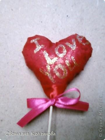 Скоро День Св. Валентина, воплощаю новые идей в жизнь. Решила сделать вот такое простое сердечко. Понадобятся: синтепон (его я вытащила из старой подушки, которую хотели выбрасывать), ткань красная (старый ненужный фартук), клей декоративный с блестками, лента широкая и узкая, палочка деревянная.  фото 1
