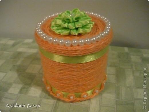 Вот такую шкатулку сделала в подарок на 8 марта. Материалы: небольшая жестяная банка из под кофе, нитки для вязания, атласная лента, бусины. Цветок на крышке сделан  в моей любимой технике Цумами Канзаши. фото 2