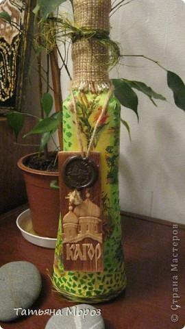 Вот такая бутылочка  Кагора готовится стать подарком к Пасхальным праздникам. Пришлось ее сначала полностью раздеть, а потом одевать.... из первоначальной одежки оставила купола церкви и название вина на висящей деревяшечке. Все остальное - новье... фото 1