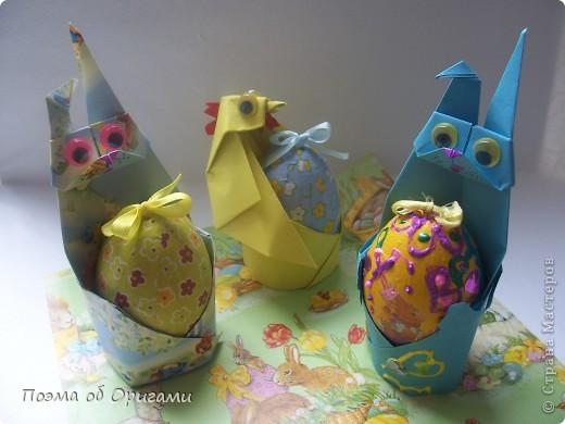 Более десяти лет назад в руках известного мастера оригами Пауло Мулатино (Германия) родилась идея декоративной подставки  для яиц . Очаровательный зайчик, трогательно прижимающий к себе пасхальное яичко оказался только началом. Обе модели складываются совсем несложно и достаточно быстро и доставят огромную радость Вам и Вашим детям. Для каждой поделки понадобится два квадрата размером 20х20.  фото 1