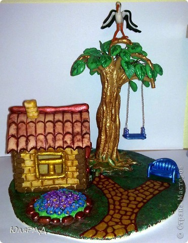 """Такой домик мы с доченькой придумали на конкурс в школу. Сначала сделала домик, но не знала куда его """"примастить"""".................так он у меня простоял почти 2 месяца. А потом сразу и дерево и качели и всё остальное появилось))) Дорожку делала витражными контурами, скамейка, аист и качели из пластики, покрасила акриловыми красками. Дерево и домик из теста))) фото 1"""