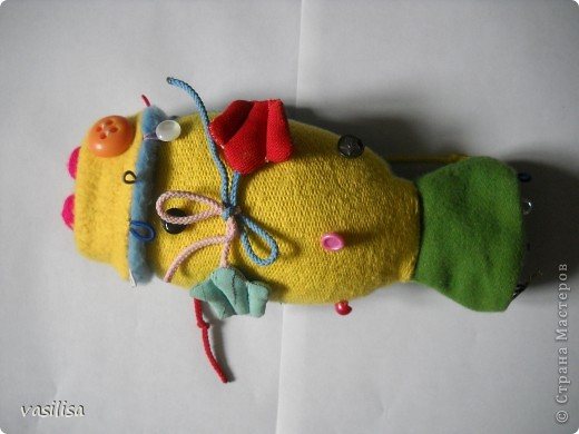 Вот и наша развивающая рыбка.  В работе использовались обрезки тканей различной структуры , пуговицы разные по величине, цветные резинки, липучки, шнурки. Рыбешка имеет голову-хвост,т.е голова легким движением руки превращается в хвост и наоборот. На голове пришиты глаза-пуговицы(размер, рельеф,цвет- самый различный), резинки-петли.  фото 1