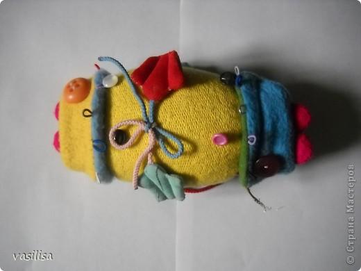 Вот и наша развивающая рыбка.  В работе использовались обрезки тканей различной структуры , пуговицы разные по величине, цветные резинки, липучки, шнурки. Рыбешка имеет голову-хвост,т.е голова легким движением руки превращается в хвост и наоборот. На голове пришиты глаза-пуговицы(размер, рельеф,цвет- самый различный), резинки-петли.  фото 2