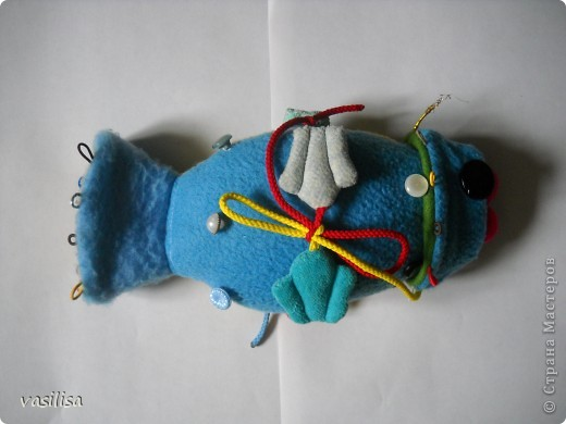 Вот и наша развивающая рыбка.  В работе использовались обрезки тканей различной структуры , пуговицы разные по величине, цветные резинки, липучки, шнурки. Рыбешка имеет голову-хвост,т.е голова легким движением руки превращается в хвост и наоборот. На голове пришиты глаза-пуговицы(размер, рельеф,цвет- самый различный), резинки-петли.  фото 3