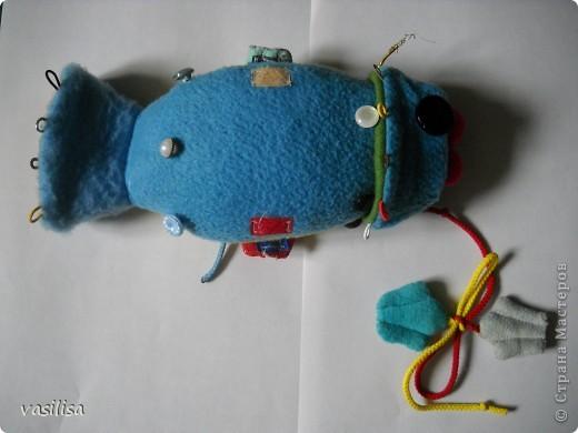 Вот и наша развивающая рыбка.  В работе использовались обрезки тканей различной структуры , пуговицы разные по величине, цветные резинки, липучки, шнурки. Рыбешка имеет голову-хвост,т.е голова легким движением руки превращается в хвост и наоборот. На голове пришиты глаза-пуговицы(размер, рельеф,цвет- самый различный), резинки-петли.  фото 4