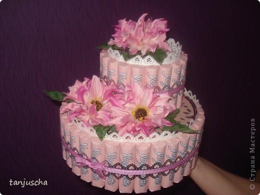 Первый раз делала тортик из конфет. Использовала конфеты Yogurette.Этот тортик сделала для своей мамы .Хочу подарить ей в воскресенье на День матери. Для тортика использовала дырокол, ленточки, цветочки искуственные, тюль. Очень хотелось сделать цветочки из гофрированной но оказалось что флористическую гофру купить в магазине очень трудно. Пришлось заказать через интернет и к сожалению она ещё не пришла.Поэтому на тортике цветочки искуственные. фото 6