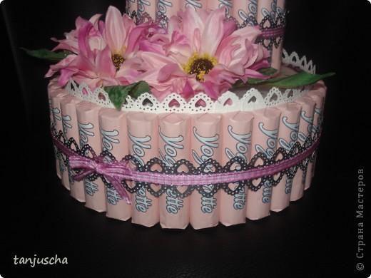 Первый раз делала тортик из конфет. Использовала конфеты Yogurette.Этот тортик сделала для своей мамы .Хочу подарить ей в воскресенье на День матери. Для тортика использовала дырокол, ленточки, цветочки искуственные, тюль. Очень хотелось сделать цветочки из гофрированной но оказалось что флористическую гофру купить в магазине очень трудно. Пришлось заказать через интернет и к сожалению она ещё не пришла.Поэтому на тортике цветочки искуственные. фото 3