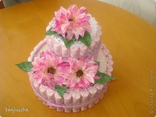 Первый раз делала тортик из конфет. Использовала конфеты Yogurette.Этот тортик сделала для своей мамы .Хочу подарить ей в воскресенье на День матери. Для тортика использовала дырокол, ленточки, цветочки искуственные, тюль. Очень хотелось сделать цветочки из гофрированной но оказалось что флористическую гофру купить в магазине очень трудно. Пришлось заказать через интернет и к сожалению она ещё не пришла.Поэтому на тортике цветочки искуственные. фото 5