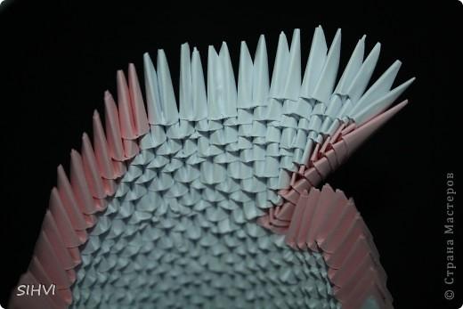 Эта увлекательная техника — создание объёмных фигур из треугольных модулей оригами — придумана в Китае. Целая фигура собирается из множества одинаковых частей (модулей). Каждый модуль складывается по правилам классического оригами из одного листа бумаги, а затем модули соединяются путем вкладывания их друг в друга. Появляющаяся при этом сила трения не даёт конструкции распасться. Поэтому собрать такого лебедя можно без клея (если вы не собираетесь его использовать как игрушку).   Чтобы собрать лебедя понадобится довольно много модулей. Поэтому, его легче мастерить большой компанией. Также, этот вид творчества отлично подходит для коллективных работ в школе. Можно экспериментировать с разными видами бумаги. Подходит офисная бумага разных цветов, мелованная цветная бумага. Иногда складывают такие фигурки из журнальных вырезок и фантиков. Плохо подходит школьная цветная бумага, т. к. она слишком тонкая, рыхлая, ломается и рвётся на сгибах.  фото 14