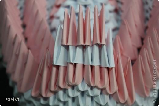 Эта увлекательная техника — создание объёмных фигур из треугольных модулей оригами — придумана в Китае. Целая фигура собирается из множества одинаковых частей (модулей). Каждый модуль складывается по правилам классического оригами из одного листа бумаги, а затем модули соединяются путем вкладывания их друг в друга. Появляющаяся при этом сила трения не даёт конструкции распасться. Поэтому собрать такого лебедя можно без клея (если вы не собираетесь его использовать как игрушку).   Чтобы собрать лебедя понадобится довольно много модулей. Поэтому, его легче мастерить большой компанией. Также, этот вид творчества отлично подходит для коллективных работ в школе. Можно экспериментировать с разными видами бумаги. Подходит офисная бумага разных цветов, мелованная цветная бумага. Иногда складывают такие фигурки из журнальных вырезок и фантиков. Плохо подходит школьная цветная бумага, т. к. она слишком тонкая, рыхлая, ломается и рвётся на сгибах.  фото 24
