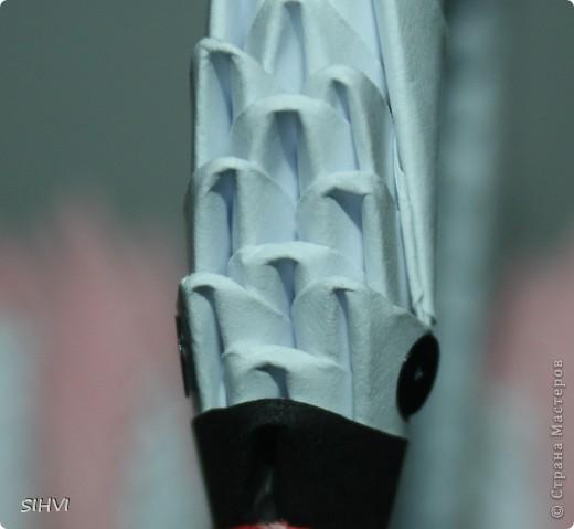 Эта увлекательная техника — создание объёмных фигур из треугольных модулей оригами — придумана в Китае. Целая фигура собирается из множества одинаковых частей (модулей). Каждый модуль складывается по правилам классического оригами из одного листа бумаги, а затем модули соединяются путем вкладывания их друг в друга. Появляющаяся при этом сила трения не даёт конструкции распасться. Поэтому собрать такого лебедя можно без клея (если вы не собираетесь его использовать как игрушку).   Чтобы собрать лебедя понадобится довольно много модулей. Поэтому, его легче мастерить большой компанией. Также, этот вид творчества отлично подходит для коллективных работ в школе. Можно экспериментировать с разными видами бумаги. Подходит офисная бумага разных цветов, мелованная цветная бумага. Иногда складывают такие фигурки из журнальных вырезок и фантиков. Плохо подходит школьная цветная бумага, т. к. она слишком тонкая, рыхлая, ломается и рвётся на сгибах.  фото 26