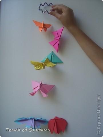 Подвеска состоит из семи видов бабочек. Каждая из них складывается очень просто, а потому, эта композиция отлично подходит для занятий с детьми. К тому же, хоровод из пестрых красавец украсит любой дом, и станет приятным напоминанием о теплом  лете. Подвеска из фигурок крепится на пластмассовый браслет с помощью лески.  фото 1