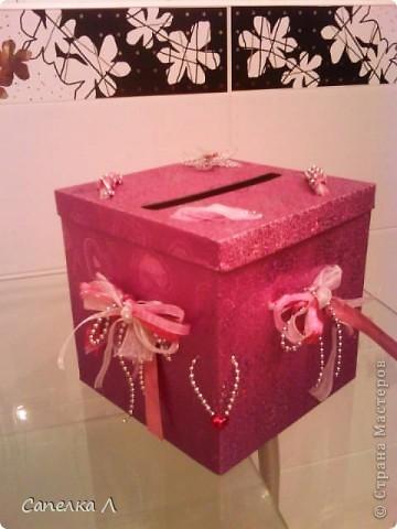 Была просто розовая подарочная коробка, которую попросили украсить. Взяла  ленточки атласные и из органзы, елочные серебристые бусы, продела их сначала в дырочки на крышке, а потом стала разводить по бокам, также продевая в дырочки, завязала бантами, чем зафиксировала крышку. фото 1