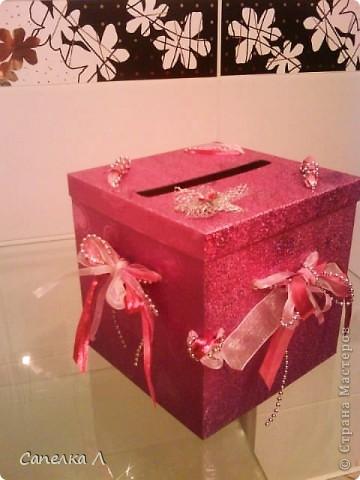 Была просто розовая подарочная коробка, которую попросили украсить. Взяла  ленточки атласные и из органзы, елочные серебристые бусы, продела их сначала в дырочки на крышке, а потом стала разводить по бокам, также продевая в дырочки, завязала бантами, чем зафиксировала крышку. фото 2