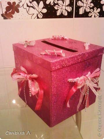 Была просто розовая подарочная коробка, которую попросили украсить. Взяла  ленточки атласные и из органзы, елочные серебристые бусы, продела их сначала в дырочки на крышке, а потом стала разводить по бокам, также продевая в дырочки, завязала бантами, чем зафиксировала крышку. фото 3