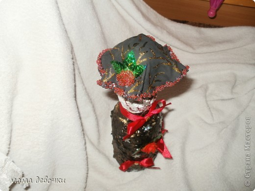 Ох и намучалась я с этой бутылочкой, изначально хотела сделать замок,  для этого покрыла бутылочку шпатлевкой, но что -  то получилось не очень и с помощью ножа нанесла рельеф, когда шпатлевка высохла покрасила в розовый цвет и решила сделать декупаж  ромашки, когда высохли салфетки, рисунок потерялся в розовых оттенках, потом покрасила ее в черный цвет и посыпала бронзой, хотела сделать даму, ну что то  идея не получилась, надоело мне смотреть на эту неудавшуюся бутылочки и решила задекорировать ее вот так. Выставлять напоказ не хотела, муж настоял, сказал только, темная бутылочка получилась, но на кухню сойдет! Что получилось, судите сами! Всем спасибо!  фото 4