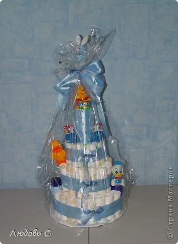 Делали сотруднице на рождение мальчика. На торт ушло 72 памперса, игрушки, 5 м атласной ленты. По центру проходит лист бумаги для акварели скрученый в трубку, в него положены буылочка и ползунки с кофточкой.