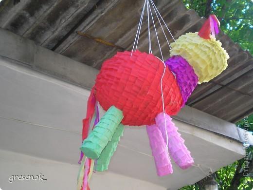 Эту игрушку я делала сыну на день рождения из обычных воздушных шариков, оклеенных бумагой. Внутри туловища и головы - конфеты. Игрушку подвесили, детям (5 лет и 3 года) вручили палку, которой они били лошадь (да-да, это Лошадь :)), для пущего веселья гость, залезший на лестницу, дергал пиньяту так, чтоб детям было сложнее в нее попасть. По идее, из пробитой дырки должны были высыпаться конфеты и обрезки цветной бумаги, но наша веревка не выдержала  неожиданно сильных ударов детей, поэтому добивали коня на полу... фото 2