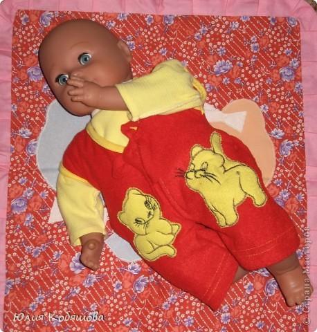 Снова одежда для Дашиного Женечки.  Была у моей девочки безрукавочка, когда она была еще совсем малюсенькая, а на ощупь такая мягенькая, такая приятная, вот  лежала она у нас лет 7 и решила я пошить из нее комбинезончик для любимой куклы дочки. Вот что получилось, Женька рад обновке, Даша довольна и как обычно просит что-нибудь еще, так что буду думать, что пошить в след. раз, благо еще есть некоторые маленькие костюмы от Дашеньки, наверное скоро займусь их перешивкой, а потом похвалюсь. фото 2