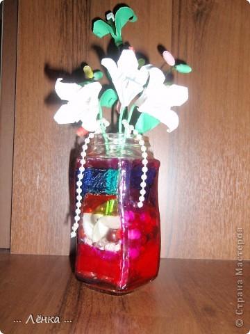 """Вот такая вазочка у меня получилась! Баночку раскрасила витражными красками. Сделала из бумаги лилии и веточку с листиками и """"бусинами"""" из бумаги. В баночку накидала всякие ненужные мелочи (бусинки, бисер, скрепочки и другое) получилась такая яркая композиция)) фото 2"""